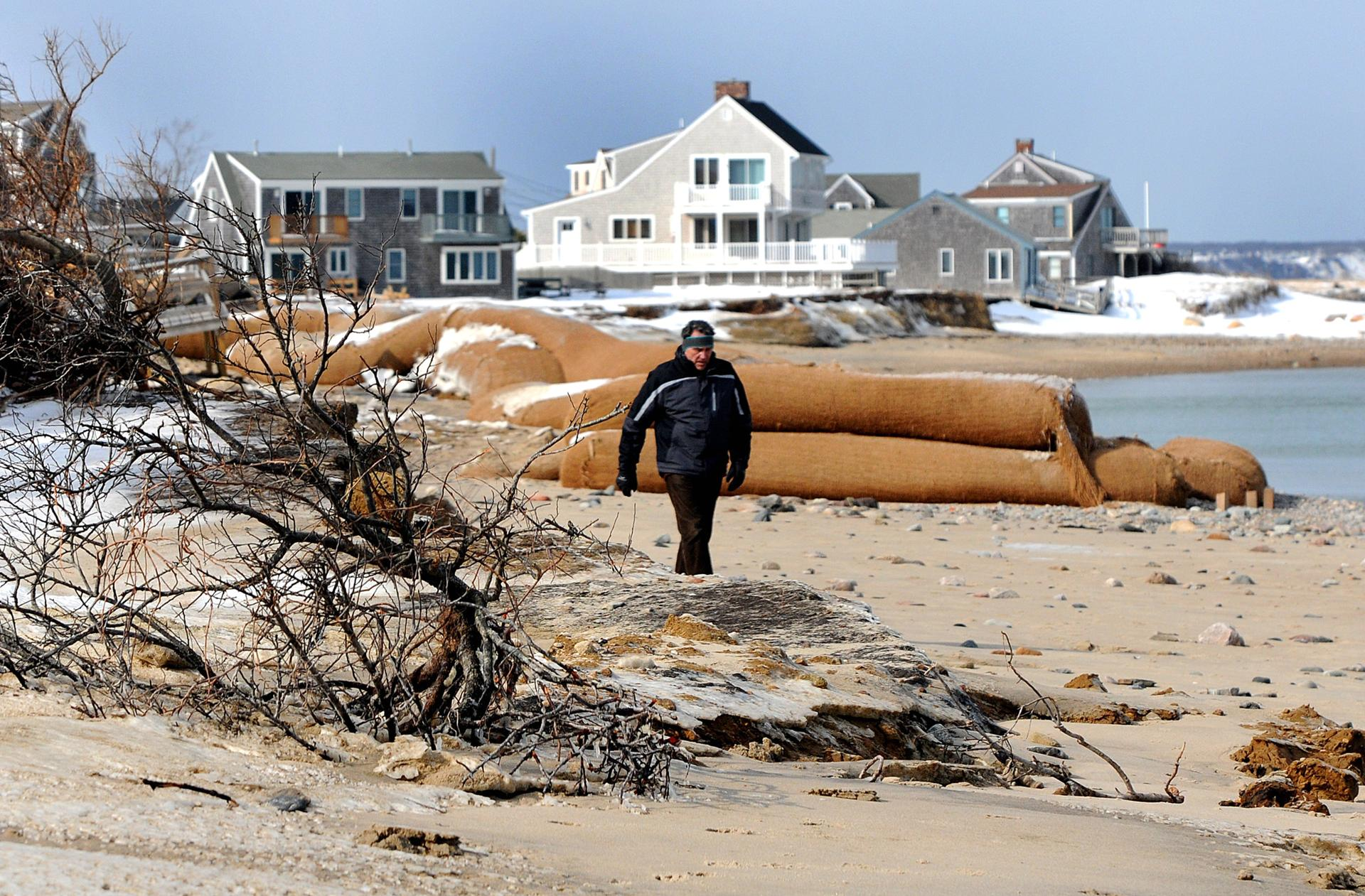 Steve Adamic walked along a Sandwich beach. Residents say the Cape Cod Canal has eroded Sandwich's beaches and exacerbated flooding.